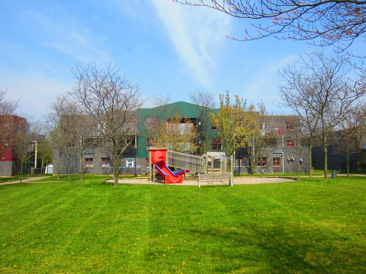 Picture of a playground in front of residence buildings at 78 College Ave.