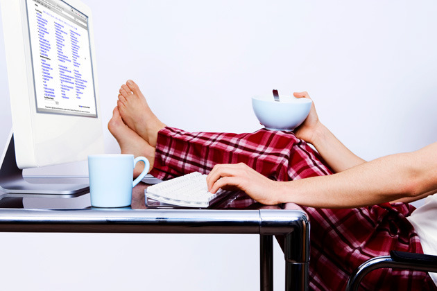Picture of a person with their feet up on their desk, looking at a computer screen and holding a bowl.